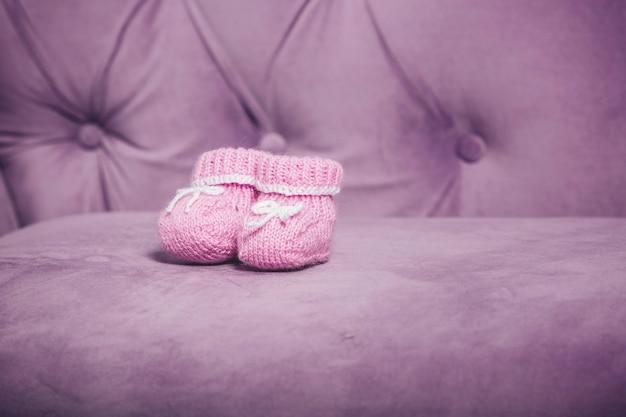ソファの上に立っているピンクのニットの小さな赤ちゃんのブーツのクローズアップ