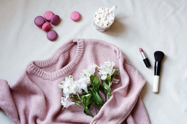 Pink knitted sweater, cosmetic products and white flowers