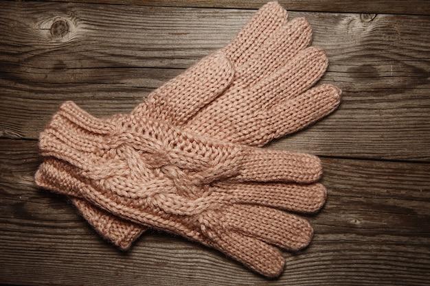 古い素朴なピンクのニットの暖かい手袋