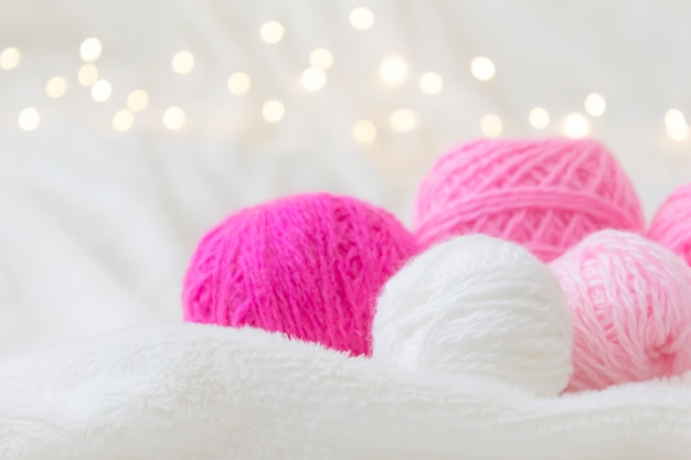 Pink knitting balls lie on a light background