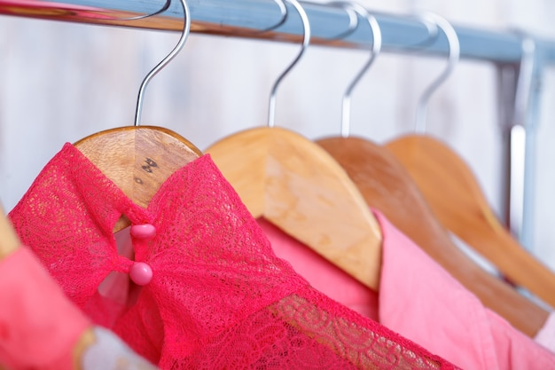 Розовая кружевная женская блузка на деревянных вешалках на стойке в магазине модной одежды. яркий женский шкаф крупным планом