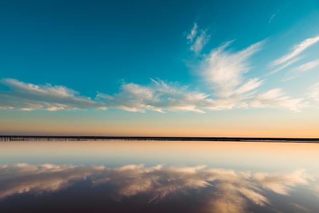 雲と青い空の下に海の湾とピンクの湖と砂浜