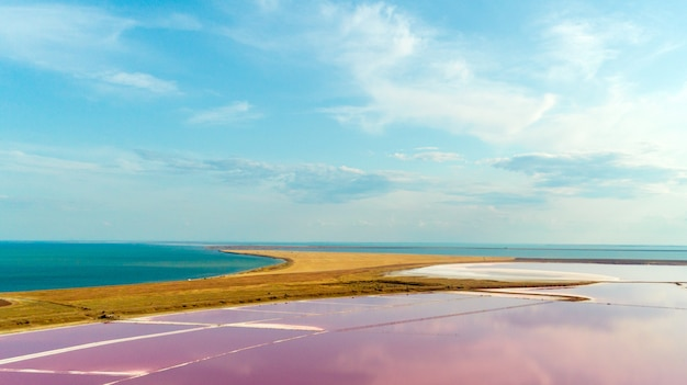 Pink lake and sandy beach with a sea bay under a blue sky with clouds