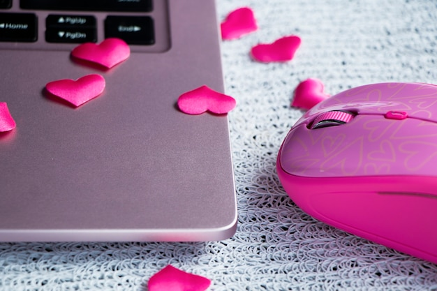 Pink laptop keyboard pink laptop mouse on a light table with scattered hearts finding love online