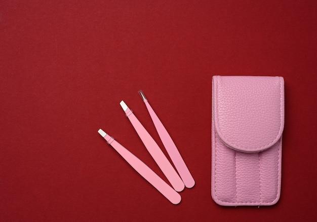 Розовый кожаный чехол с различными металлическими пинцетами для бровей, вид сверху