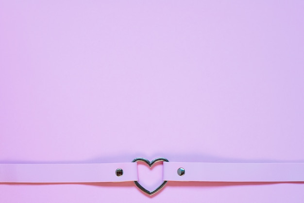 Pink leather choker with a metal heart. valentine's day concept.