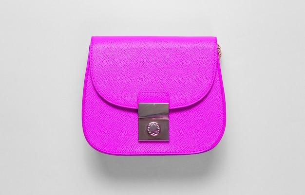Розовая кожаная мини-сумка на синем фоне. концепция моды минимализм. вид сверху