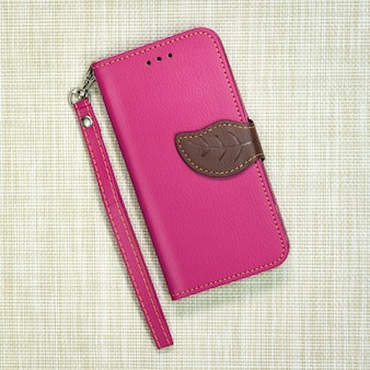 Pink leather phone case on weave background. fashion mobile phone cover.