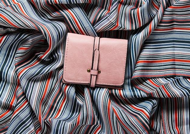 직물 표면에 핑크색 가죽 지갑.