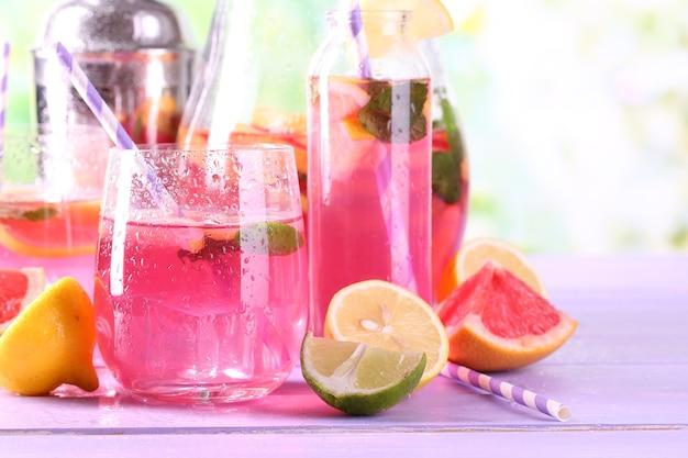 Розовый лимонад в очках и кувшин на столе крупным планом