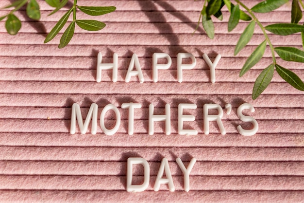 Pink letterboard with quote happy mother's day, decorated with green leaves on pink background.