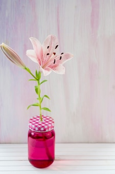 Pink lily flower in pink transparent jar on wooden table