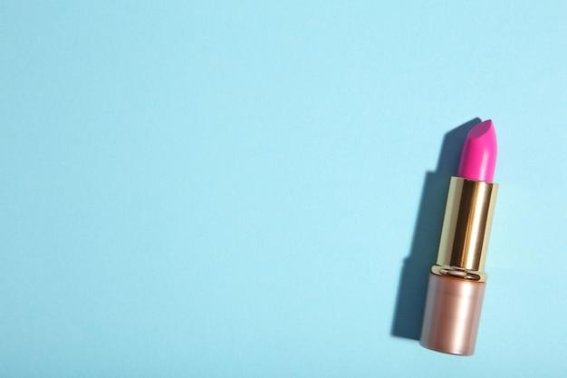 Pink lipstick on blue background, flat lay