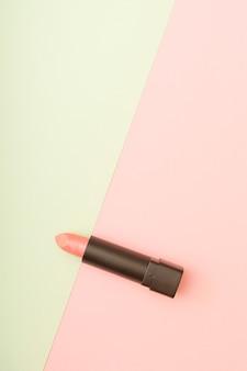 パステルピンクと緑の背景の組み合わせのピンクの口紅。メイク化粧美容ケアのコンセプト。コピースペースのあるフラットレイ写真。