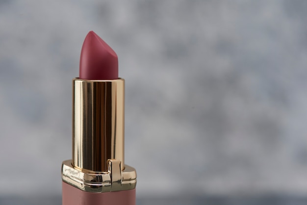 Pink lipstick on a marble surface with a white background with gray