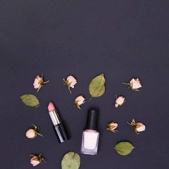 Pink lipstick and nail varnish bottle surrounded with pink rose buds and leaves on black background