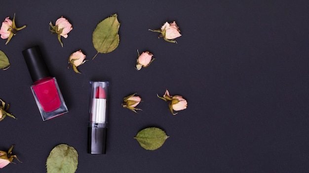 Pink lipstick and nail varnish bottle with pink dry rose buds and leaves on black background