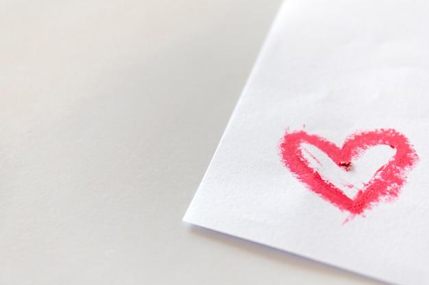 Розовая помада, смазанная в форме сердца на белой бумаге на белом столе.