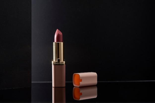 芸術的な黒い背景のサイドライトとテキスト用のスペースを備えたピンクの口紅