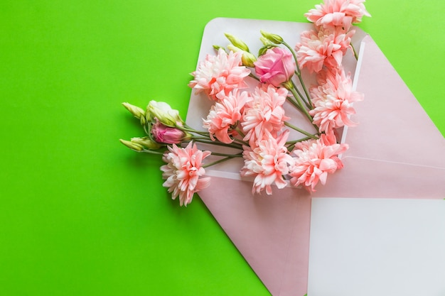 Pink lisianthus and chrysanthemums in envelope on green background. mother's day, wedding invitation.