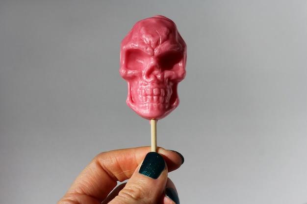 Розовый леденец на палочке в форме черепа на палочке на сером фоне. концепция хэллоуина