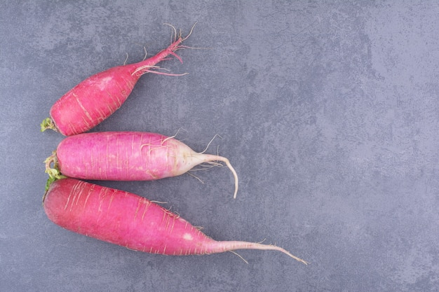 Pink long radish isolated on concrete background.