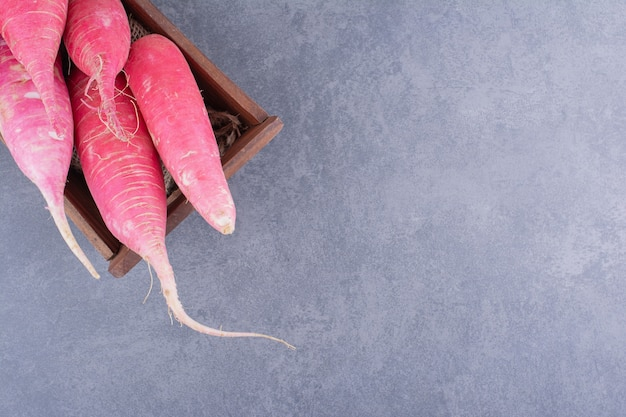 Pink long radishes isolated on concrete surface