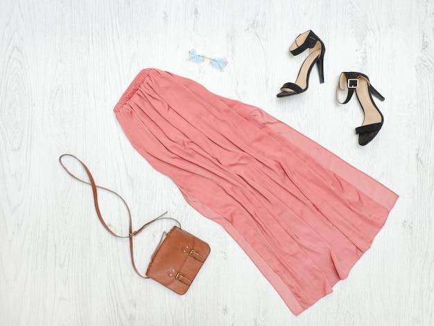 Розовая длинная юбка, сумочка и солнцезащитные очки. модная концепция