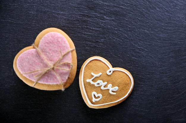 Розовое любовное печенье на темном столе, крупным планом