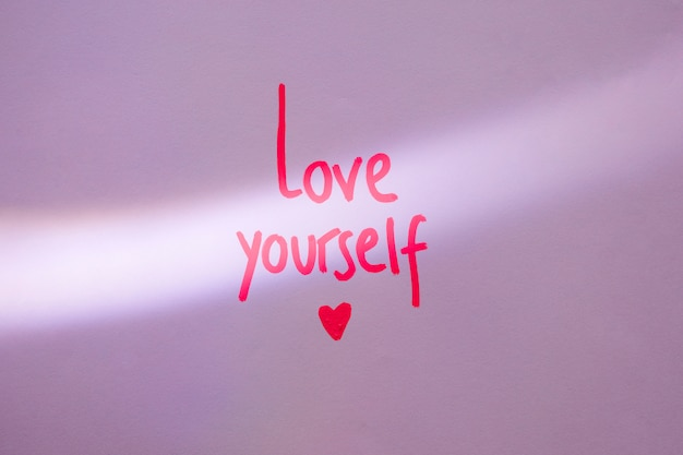 Pink love yourself inscription on purple table