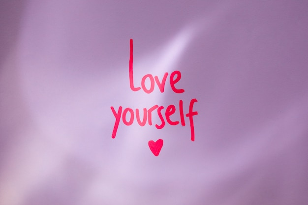 Pink love yourself inscription on table