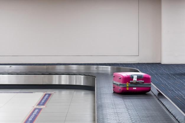 Pink luggage on the belt conveyor.