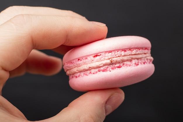 手にピンクのマカロンクッキー