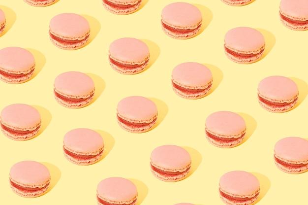 黄色の背景にパターンで配置されたピンクのマカロン。甘い食べ物のケーキのコンセプト