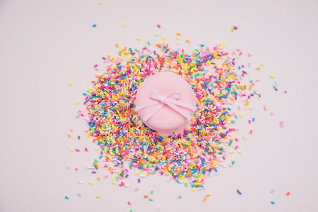 Pink macarons over the colorful sprinkles on colored background