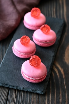 Pink macarons - sweet meringue-based confection decorated with fresh raspberries