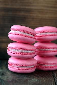ピンクのマカロン - 木製のテーブルの上の甘いメレンゲ ベースのデザート