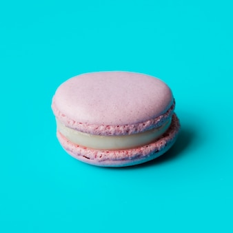 Pink macaroon with cream on blue background