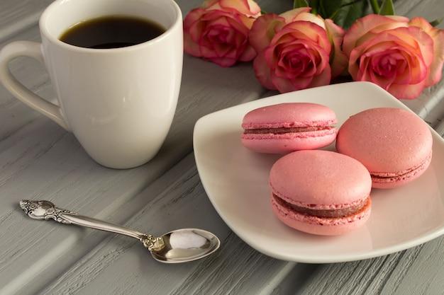 灰色の木の表面にピンクのマカロンとコーヒー