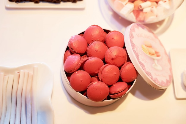 Pink macaroons in a box on candy box at a restaurant.