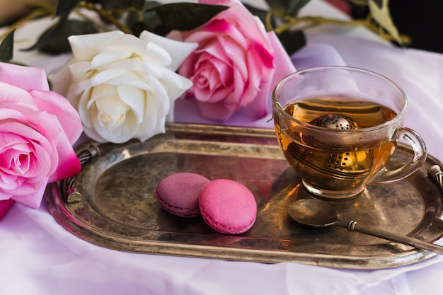 Pink macaroons, hot tea on silver vintage tray blurred roses background