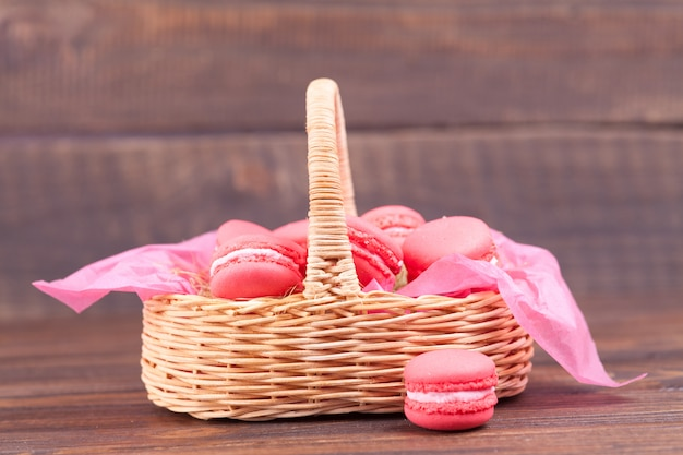 Pink macaroons in a wicker basket on a dark wooden .