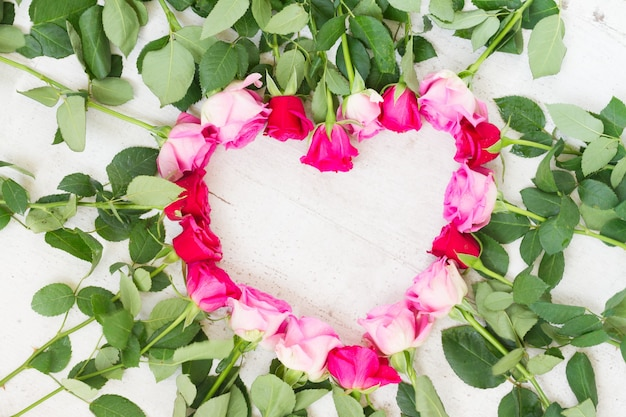 Pink and magenta fresh roses frame in heart shape on white wooden aged background