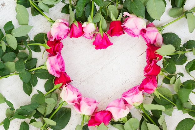 Pink and magenta fresh roses frame in heart shape on wooden aged background