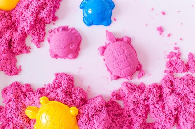 Розовый волшебный песок сформировал черепаху и рыбу на белом космосе. раннее сенсорное образование. готовимся к школе. развитие