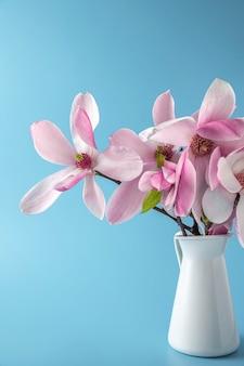 Букет розовых цветов магнолии в вазе на синей поверхности