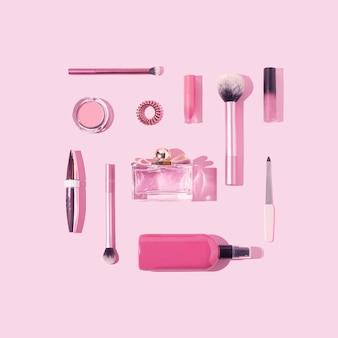 明るいパステルカラーの背景にピンクのメイクアップと美容製品フラットレイ構成