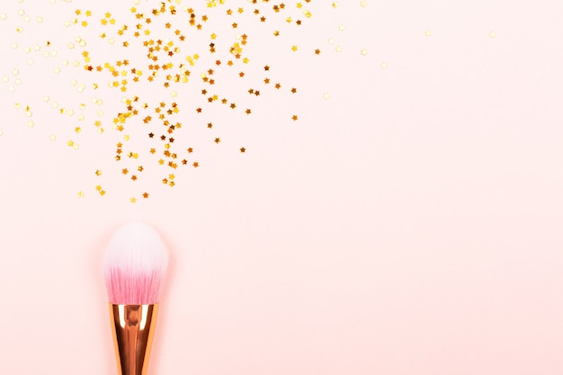 Pink makeup brush and confetti