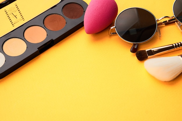 Розовая губка для макияжа и пудра, желтый фон и солнцезащитные очки