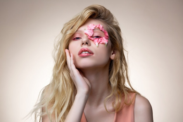 ピンクのメイク。ピンクのメイクをしているピンクのドレスを着ている優しいブロンドの髪の魅力的なモデル